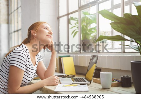 Young woman sitting daydreaming at the office leaning her chin on her hand and staring up out of a nearby window with a dreamy smile of pleasure Stock photo ©