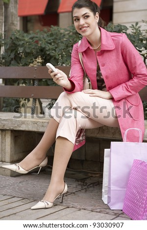 Young woman sitting down on a bench with her shopping bags, using a cell phone.