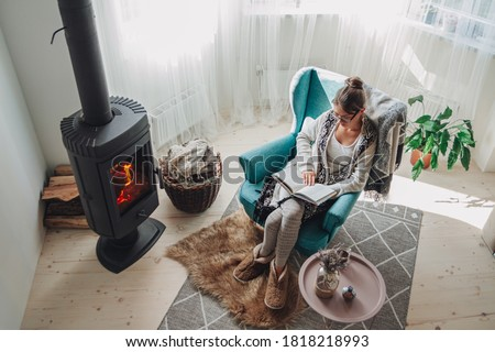 Young woman sitting in a cozy armchair with a warm blanket reading a book Stock fotó ©