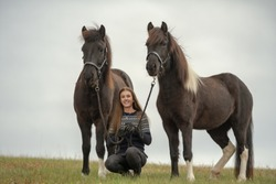 Young woman sitting in a field with her two best friends. Her Icelandic horses. With white background