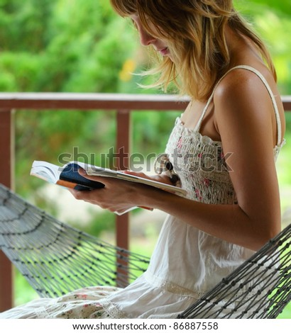 Young woman sitting in a hammock in a garden and reading a book