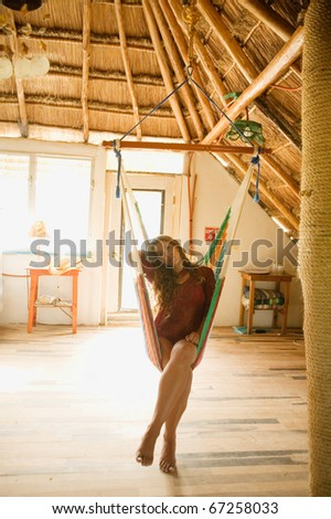 Young woman sitting in a hammock indoors