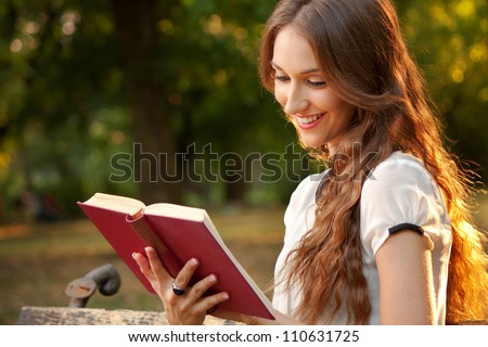 Young woman sitting in a park and reading a book