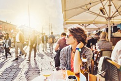 Young woman sitting in a street cafe drinking beer and watching the city life, Europe lifestyle. Denmark, Copenhagen, Nyhavn