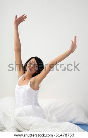 young woman sitting in bed and strech her body