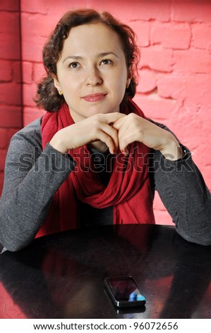 Young woman sitting in cafe with mobile phone, dreaming