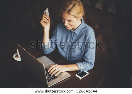 Young woman sitting in cafeteria and perform online shopping #526841644