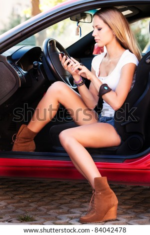 young woman sitting in car with mobile phone