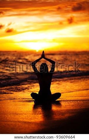 Young woman sitting in lotus position doing yoga on the ocean shore