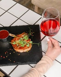 Young woman sitting in restaurant alone and eating meat steak with a glass of red wine. Eat out in restaurant concept, social distancing due to worldwide covid-19 pandemic.