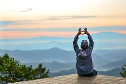 Young woman sitting in summer mountains and making heart shape with her hands,copy space.