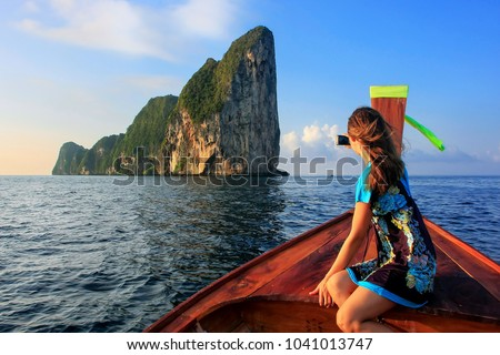 Young woman sitting in the front of a longtail boat going to Phi Phi Leh Island, Krabi Province, Thailand. This island is part of Mu Ko Phi Phi National Marine Park.