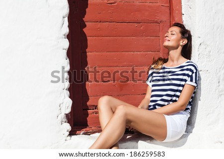 Young woman sitting in the front of the door, eyes closed, day dreaming.Copy space
