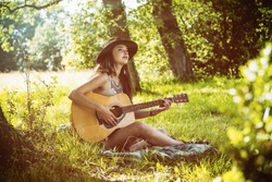 Young woman sitting in the grass playing the guitar