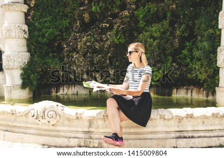 young woman sitting near historical fountain with map and searching location