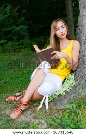 Young woman sitting near the tree and reading a book