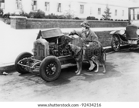 Young woman sitting next to small car looking at the engine with her German shepherd
