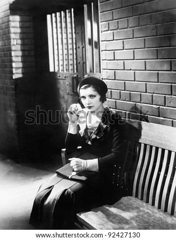 Young woman sitting on a bench in front of a jail cell