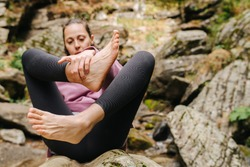 Young woman sitting on a big stone looking on her bare foot, holding it. She's wearing yoga pants and pink hoodie.