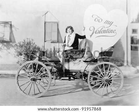 Young woman sitting on a car holding a big heart shaped sign