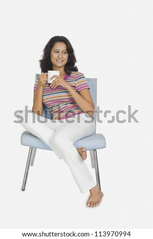 Young woman sitting on a chair and drinking tea