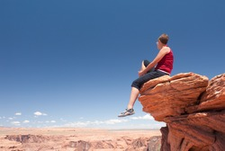 Young woman sitting on a rock in Arizona. USA