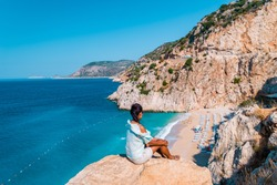 young woman sitting on a rock looking out over the cliff of Kaputas Beach Turkey Mediterranean Sea by Kas, View of the Kaputas Beach, Turkey