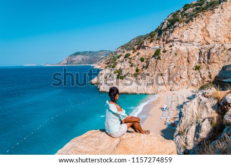 young woman sitting on a rock looking out over the cliff of Kaputas Beach Turkey Mediterranean Sea by Kas, View of the Kaputas Beach, Turkey #1157274859