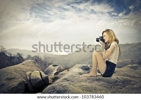 Young woman sitting on a rock on a hill and taking pictures with a camera