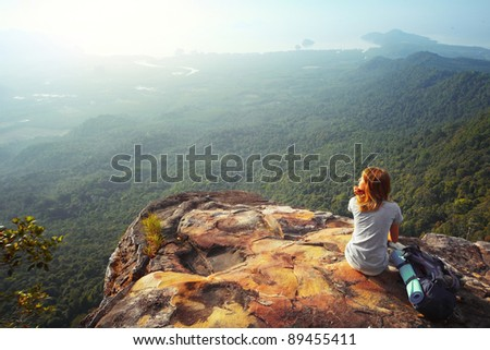 Young woman sitting on a rock with backpack and looking to the horizon