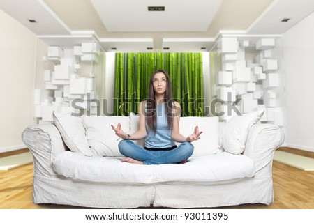 Young woman sitting on a sofa in the lotus position meditating in a zen environment #93011395