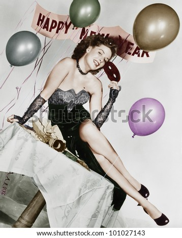 Young woman sitting on a table with balloons and sign