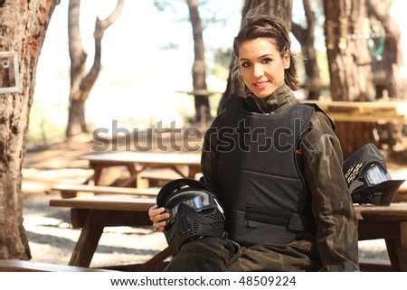 Young woman sitting on bank with helmet on legs, getting ready for paintball match