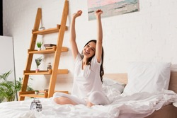 young woman sitting on bed and stretching near retro alarm clock