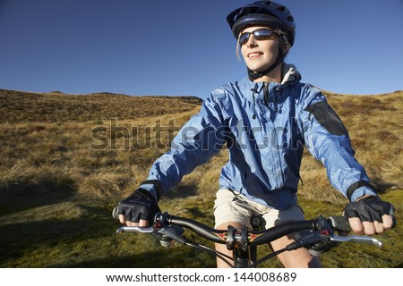 Young woman sitting on bicycle in field against clear blue sky