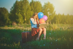 Young woman sitting on big suitcase on wild meadow with colored balloons holding laptop. Travel guide, Buy Tickets, online shopping, enjoy freedom