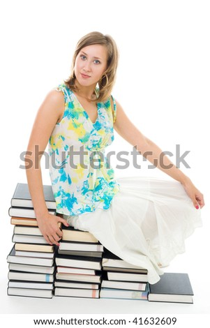 Young woman sitting on books in summer casual clothes looking to camera and smilie