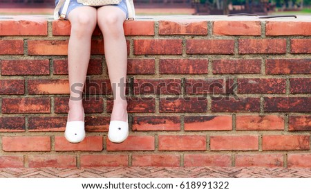 Young woman sitting on brick wall #618991322