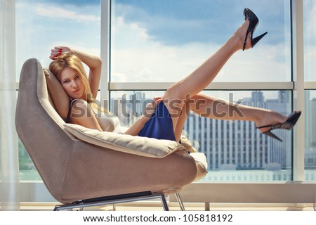 Young woman sitting on chair on window background.