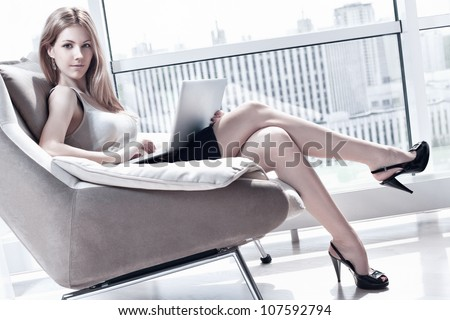 Young woman sitting on chair with laptop. Bright white colors.