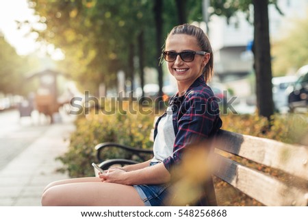 Young woman sitting on city bench with her cellphone