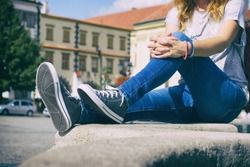 Young woman sitting on city fountain dressed in jeans and sneakers. Dark grey trendy footwear. A hipster girl in old european town.