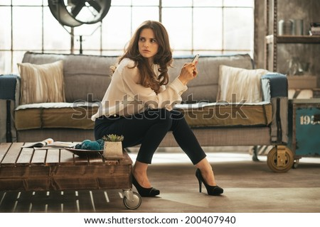 Young woman sitting on coffee table in loft apartment #200407940