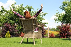 Young woman sitting on comfortable chair in park