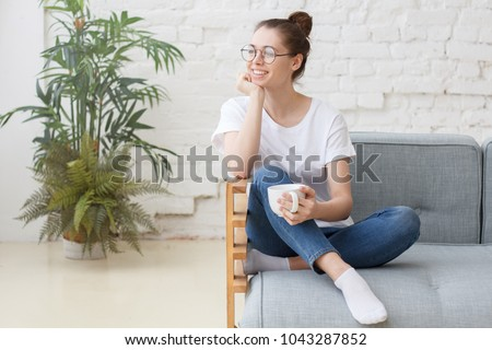 Young woman sitting on couch, chilling, drinking hot coffee and enjoying morning, takes break at home