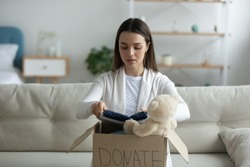 Young woman sitting on couch preparing parcel for sending to needy human. Girl with big kind heart puts used clothes new wear and soft bear toy in donation box, concept of caring about homeless people
