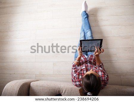 Young woman sitting on floor and using notebook.View from above.