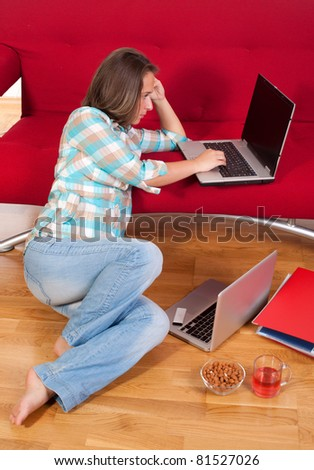 young woman sitting on floor at home in living room using her laptop