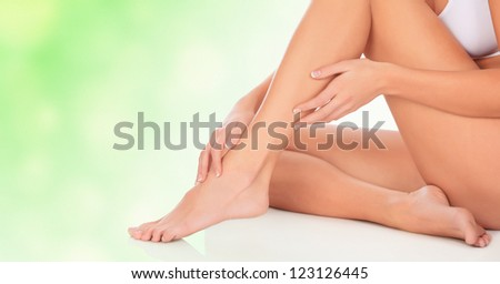 Young woman sitting on floor, green blurred background