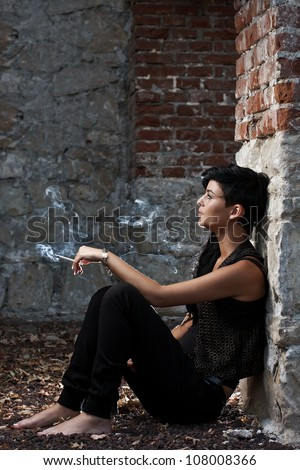 Young woman sitting on floor holding cigarette